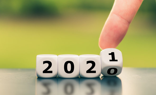 "Hand turns a dice and changes the year ""2020"" to ""2021""."