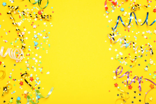 Colorful ribbons with paper stars and confetti on yellow background