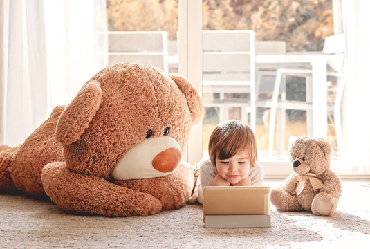 Cute little child watching cartoons on digital tablet device lying on floor with two soft teddy bear toys at home. Modern childhood.