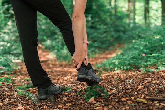 Female hiker with ankle injury in forest