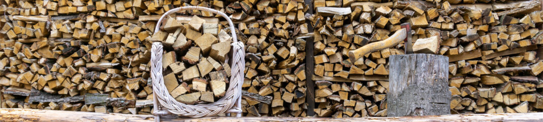 Basket with firewood on wooden background. In a natural light..A basket loaded with chopped wood stands in front of a wall of firewood.