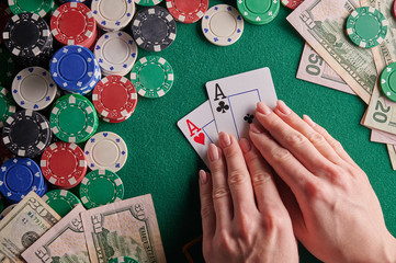 A player in a poker casino shows a pair of aces against the background of chips and money of dollars. Victory, success. Gaming business.