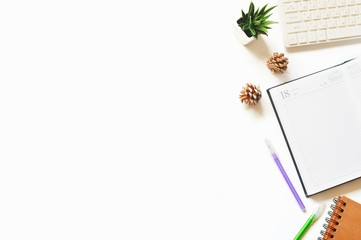 White computer keyboard, open paper notebook, purple and green pens, pine cones and decorative plant. Mockup, free space for text. Flat lay photo modern office table with stationery