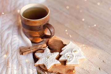 Christmas still life. Cup of tea, gingerbread glazed cookies, cinnamon at wooden background with glares. Cozy tea time with homemade sweets and mug of hot beverage. Winter food, drink, new year lights
