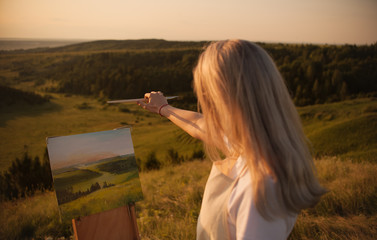 The artist paints a picture outdoors in the early sunny morning. Painting in nature.
