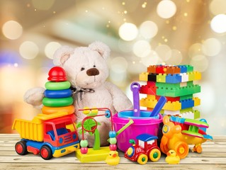 Bear and colorful toys on a wooden desk on abstract light background