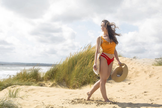 Beautiful woman walking at the beach, enjoying the breeze