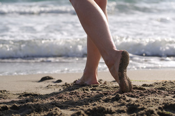 Women's feet waking on the sand near the waves of the sea