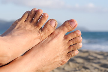 Women's feet with natural nails with a beach background