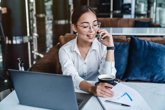 Woman entrepreneur managing her business from office lobby working on laptop computer and discussing business using smartphone