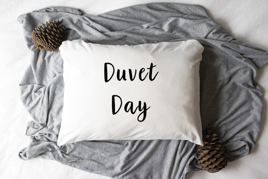 """""""Duvet Day"""" text written on a white pillow with autumn/winter props - Christmas hipster concept"""