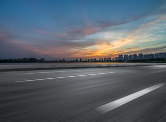 Asphalt road and the beautiful urban skyline at sunset Fotomurales