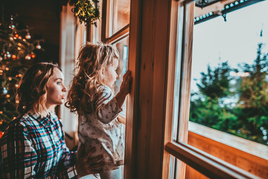 Mother and Daughter Having Fun on Christmas Morning. Precious family moment, young mom playing with her toddler daughter by decorated Christmas Tree and the window, winter landscape.