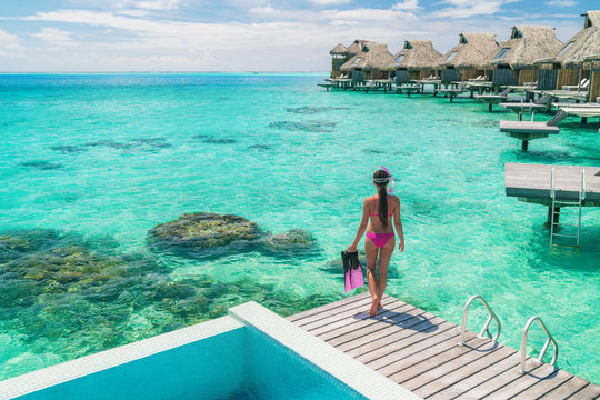 Luxury overwater bungalows Tahiti resort woman going snorkeling from private hotel room on Bora Bora island, French Polynesia. Travel vacation recreational activity watersport fun leisure.