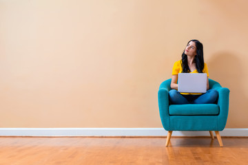 Young woman with a laptop computer in a thoughtful pose sitting in a chair Wall mural