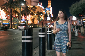 Poster Las Vegas happy woman traveler walking in streets of Las Vegas at dark night. smiling young girl tourist holding cellphone and relax on road in evening. female in dress sightseeing in busy modern area urban