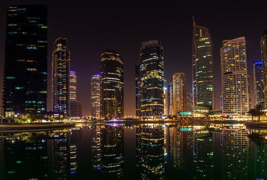 25 October 2019; Jumeirah Lake Towers, Dubai, United Arab Emirates; View of skyscrapers at night with reflections on the lake.dng