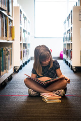 Young Girl Reads on the Floor of Library