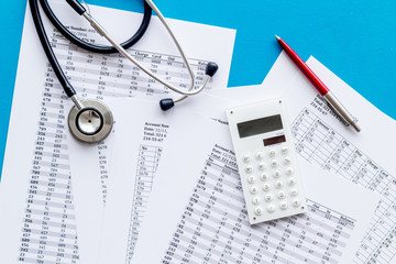 Health insurance concept. Stethoscope near financial documents and calculator on blue background top view