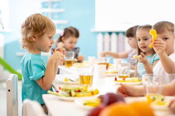 Group of children have dinner. Kids eating healthy food in kindergarten.