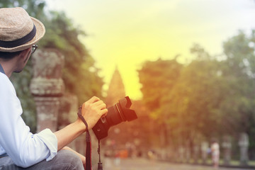 Photographer holding DSLR camera and sitting at  Prasat Phnom Rung in Phnom Rung Historical Park that important Khmer ancient monument in Buriram province, Thailand.