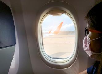 Sick woman wear face mask sit on passenger economy seat near cabin window in airplane. Passenger in departure flight plane at the airport. Novel coronavirus (2019-nCoV) infection  or Wuhan coronavirus