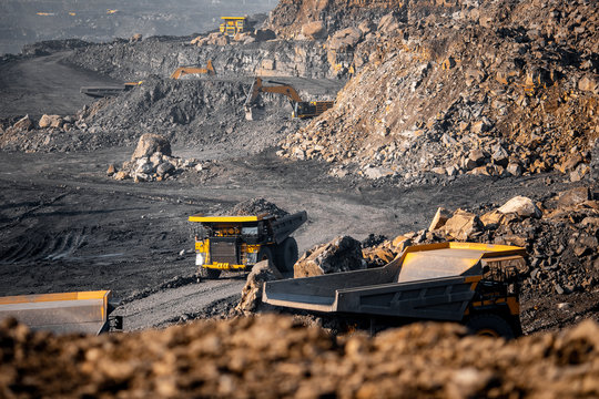 Open pit mine industry. Big yellow mining truck and excavator for coal moving on road career