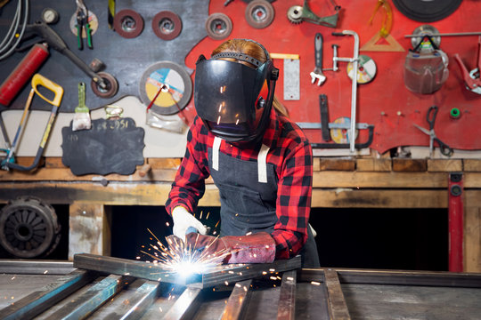 Industrial work, welder works with metal, sparks and fire on background of workplace