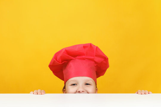 Funny little girl chef on a yellow background. The child is hiding and looking out from under the table