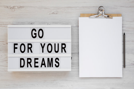 'Go for your dreams' words on a lightbox, clipboard with blank sheet of paper on a white wooden background, top view. Overhead, from above, flat lay. Copy space.