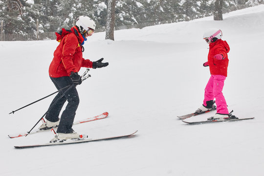 Child learning how to ski with an instructor. Winter