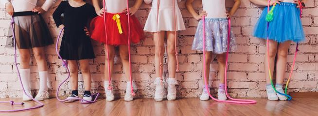 Young ballet dancers in a studio with wooden floors.