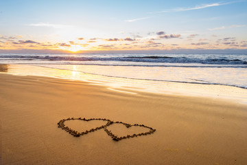 Photo sur Plexiglas Plage Valentines day on sunny beach. Two hearts drawn in sand, love concept