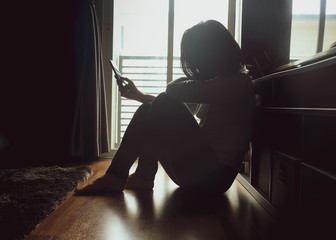 Asian woman sitting on wood floor beside window light in a dark room. Hold and bend head to look at mobile phone screen to check message, chat bad news or wait for a reply by feeling sad or hopeless