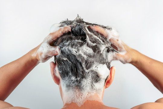 Men's hands wash their hair with shampoo and foam on white background, rear view