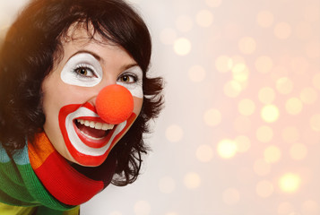 Female clown with happy joyful expression on her painted face. Copy space, studio shot.