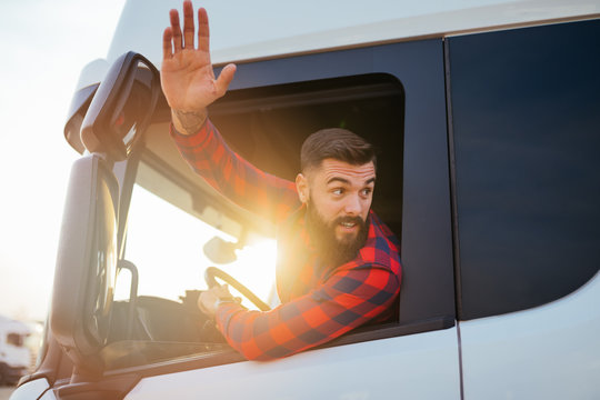 Young handsome bearded man driving his truck.