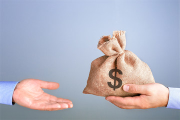 Man holds, gives a bag of money in hand like a bonus. Businessman holding bag of money in hand offering bribe with copy space. Cash bag concept.