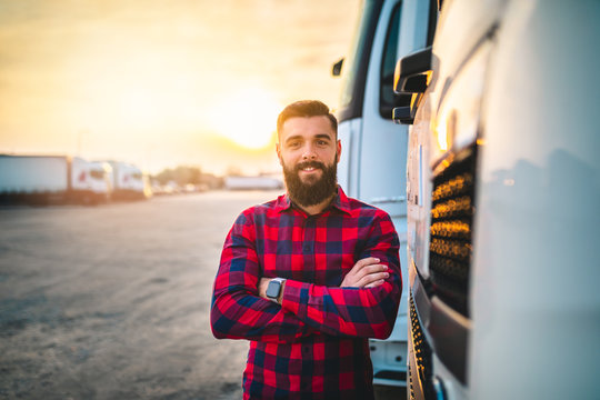 Young bearded man standing in front of his truck.