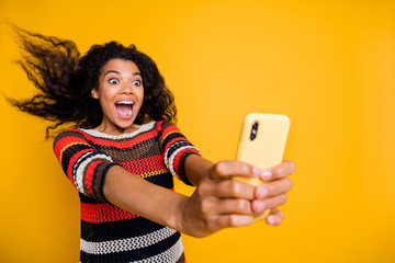 Portrait of positive cheerful afro american girl blogger ride roller coaster have her hair fly make selfie blogging video calling scream wow omg wear striped shirt isolated yellow color background
