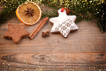 Christmas decoration on wooden background, copy space. Gingerbread cookies and spices.