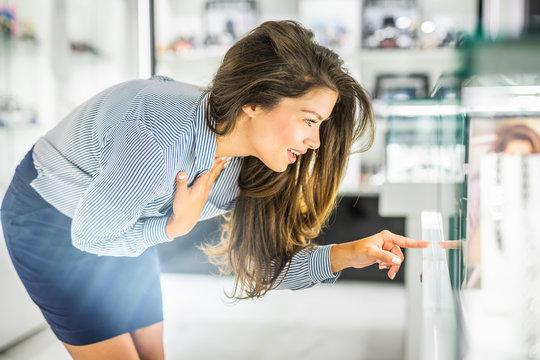 Beautiful middle age woman choosing watch in a modern jewelry store.