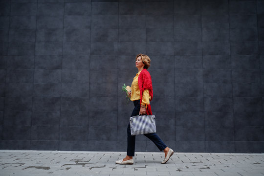 Side view of charming caucasian fashionable senior woman carrying bag and groceries while passing by gray wall.