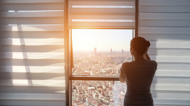 Woman is opening blinds in the morning in her modern apartment. She is looking at window with panoramic city view, sunlight