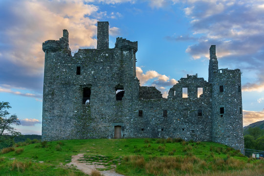 Kilchurn Castle , in the care of Historic Environment Scotland , is a ruined structure on a rocky peninsula at Loch Awe in twilight , Argyll and Bute, Scotland