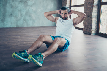 Photo of macho sportsman guy doing static sit ups sitting floor determined person sportswear tank-top shorts sneakers training house studio windows indoors
