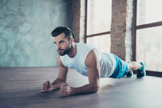 Profile photo of macho sportsman guy doing plank on elbows hands leaning floor determined sportswear tank-top shorts sneakers training house studio windows indoors