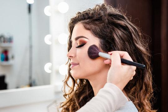 Make up artist applying professional make up of beautiful young woman.