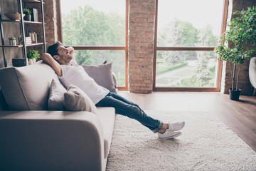 Profile photo of mixed race guy sitting cozy sofa holding hands behind head relaxing homey weekend mood looking dreamy new repair wear casual outfit flat loft living room indoors