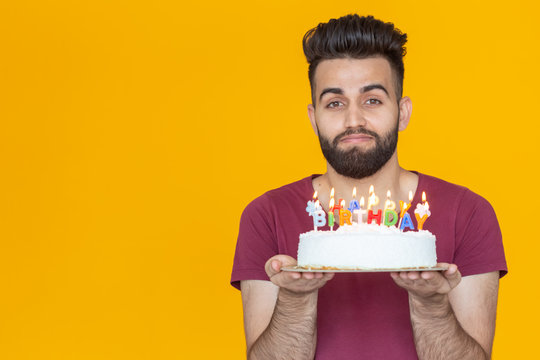 Close-up young handsome man blows off a candle from a burning cake posing for a yellow background. Holiday concept.